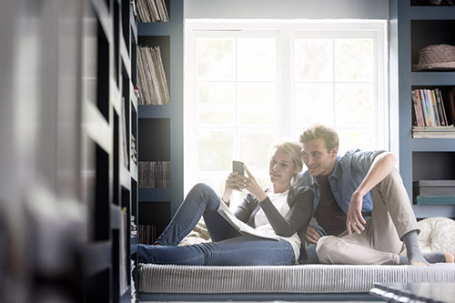 A photo of young couple using mobile phone against window. Loving partners are in brightly lit room. Both are in casuals at home